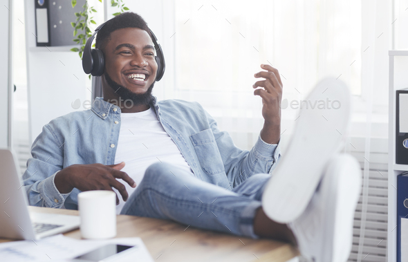 Cheerful employee relaxing at workplace, listening music and playing virtual guitar - Stock Photo - Images