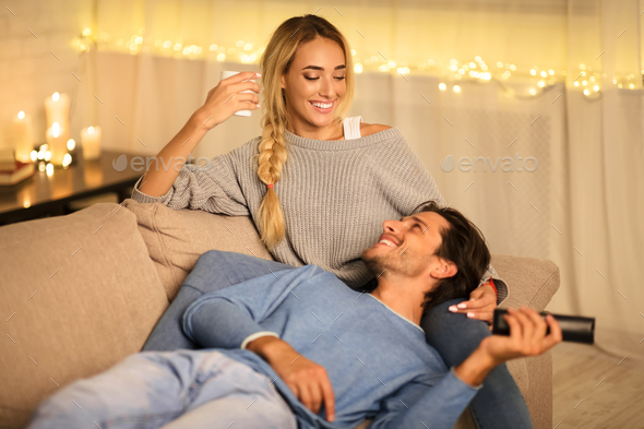 Young couple enjoying winter holidays, talking and watching tv - Stock Photo - Images