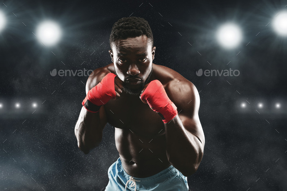Young fighter in boxing stance staying on stadium arena - Stock Photo - Images