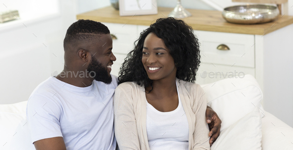 Smiling couple sitting on sofa and looking at each other - Stock Photo - Images