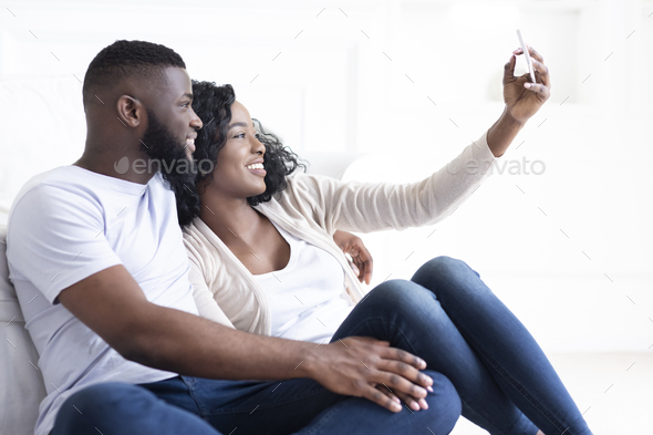 Black millennial couple taking selfie on smartphone at home - Stock Photo - Images