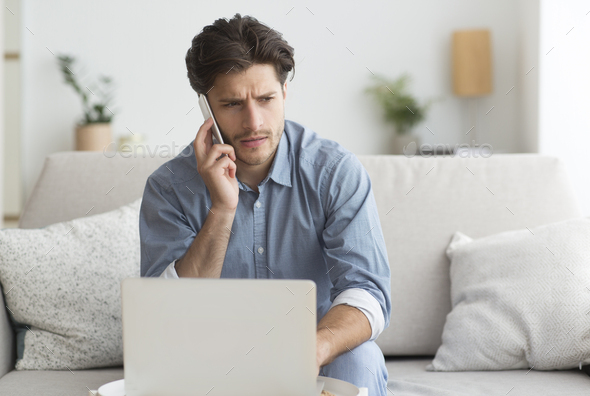 Guy Having Unpleasant Phone Conversation Working On Laptop At Home - Stock Photo - Images