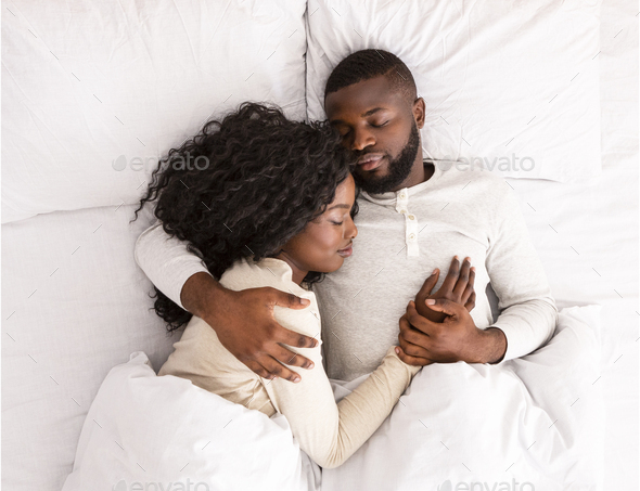 Top view of african american couple sleeping together in bed - Stock Photo - Images
