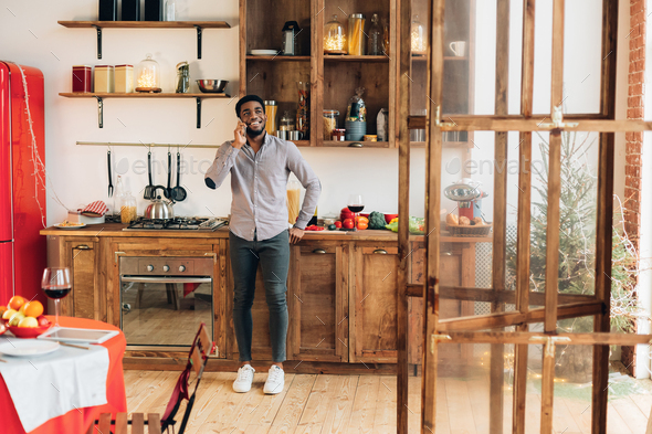 Young black man talking on mobile phone in kitchen - Stock Photo - Images