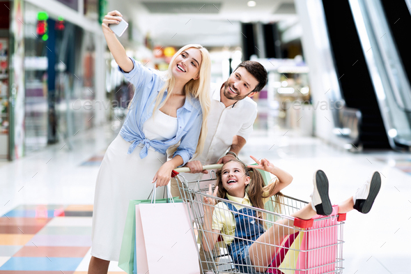 Family Taking Shopping Selfie On Smartphone Having Fun In Mall - Stock Photo - Images