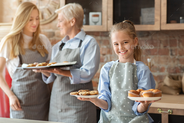 Happy girl demonstrating freshly baked home pastry - Stock Photo - Images
