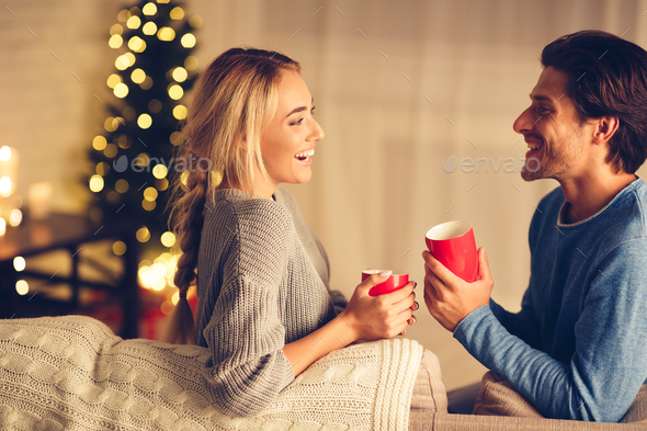 Christmas eve. Happy couple drinking tea in cozy room - Stock Photo - Images