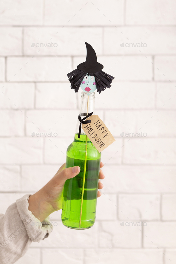 Green party drink with paper witches head over bricks wall - Stock Photo - Images
