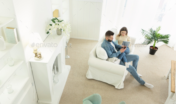 Young couple enjoying weekend, using devices on sofa - Stock Photo - Images
