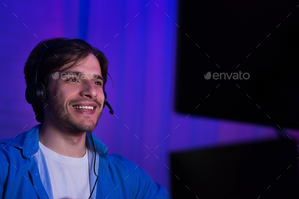 Happy young gamer in headphones playing computer game - Stock Photo - Images