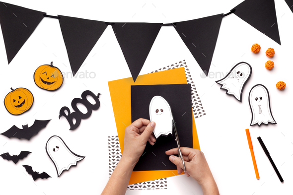 Woman cutting out cute ghosts and pumpkins on background - Stock Photo - Images