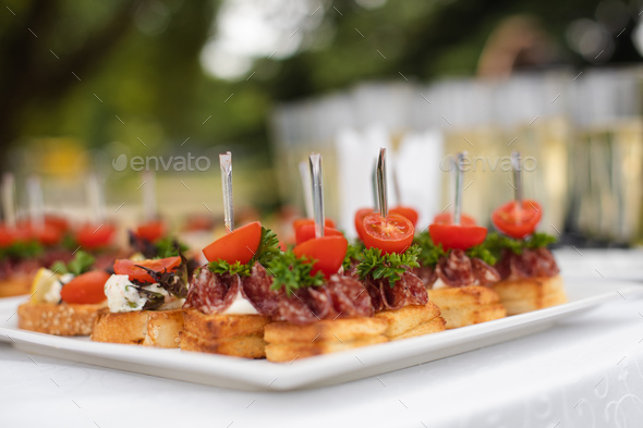 Close-up big plate with serving snack canapes fried bread tomato parsley and salami - Stock Photo - Images