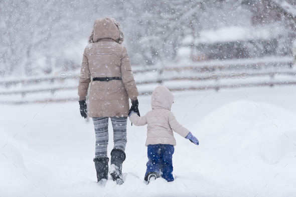 Mother with her little girl in snow - Stock Photo - Images