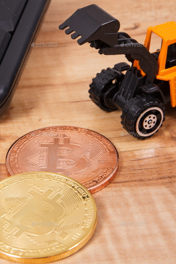 Bitcoins, miniature excavator and computer keyboard - Stock Photo - Images