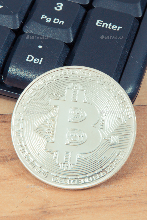 Silver Bitcoin and computer keyboard, symbol of virtual money and mining cryptocurrency concept - Stock Photo - Images