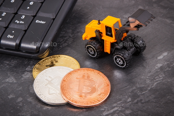 Bitcoins as symbol of electronic virtual money, miniature excavator and computer keyboard - Stock Photo - Images