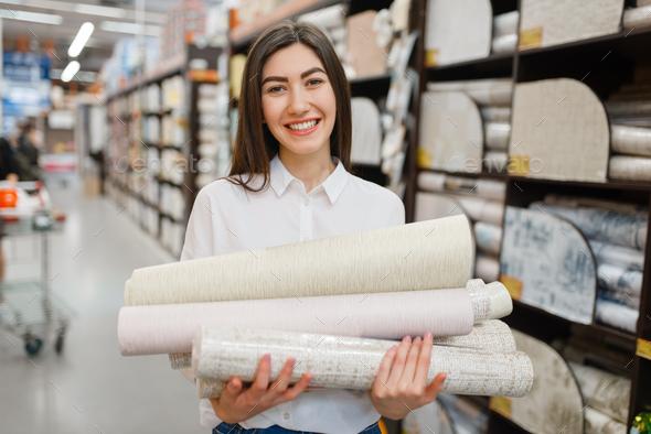 Female customer choosing wallpapers, diy shop - Stock Photo - Images