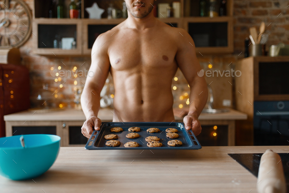 Nude man cooking pastry on the kitchen - Stock Photo - Images
