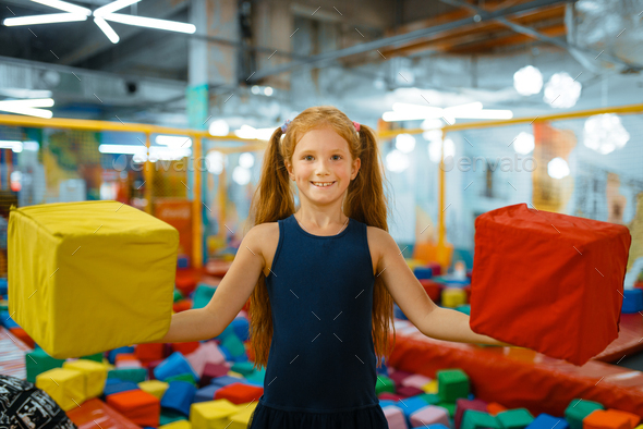 Adorable little girl playing with soft cubes - Stock Photo - Images