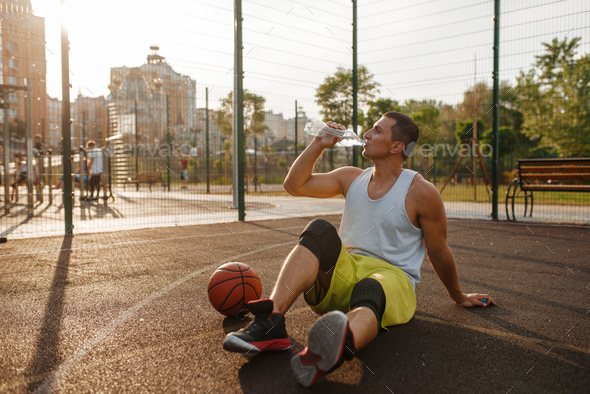 Basketball player drinks water on outdoor court - Stock Photo - Images