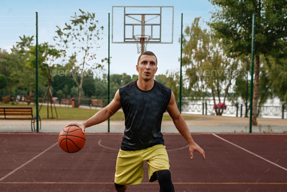 Basketball player in motion on outdoor court - Stock Photo - Images