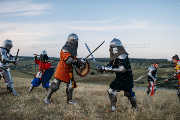 Knights in armour and helmets fight with swords - Stock Photo - Images