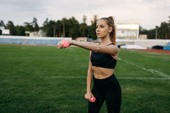 Female runner in sportswear holds dumbbells - Stock Photo - Images