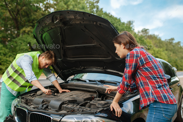 Couple at the opened hood on road, car breakdown - Stock Photo - Images