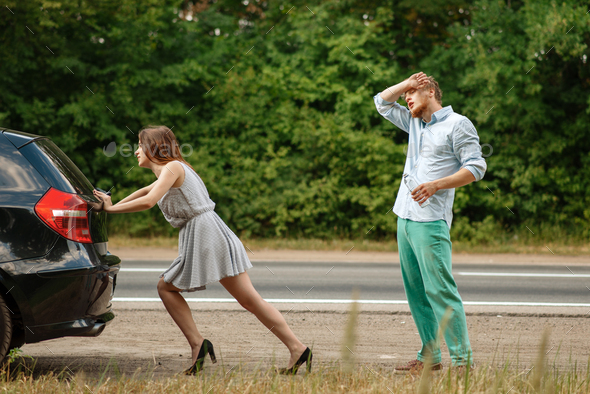 Man and woman pushing broken car on road - Stock Photo - Images
