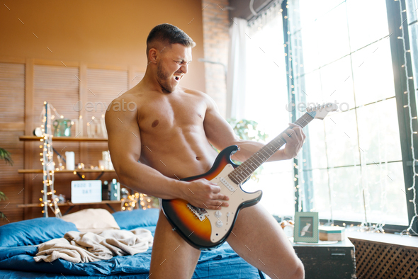 Naked man plays the electric guitar in bedroom - Stock Photo - Images
