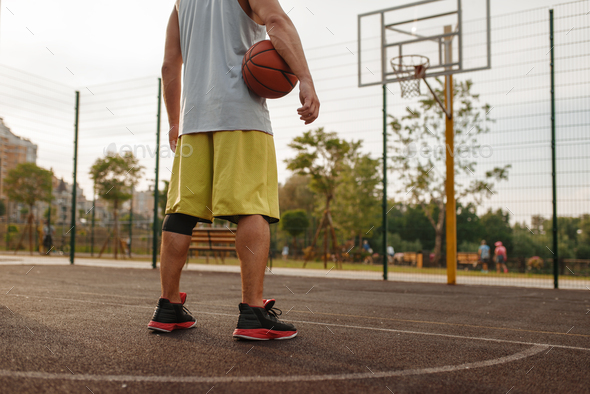 Basketball player with ball standing at the basket - Stock Photo - Images