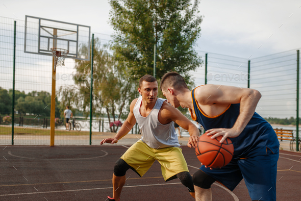 Basketball players playing intense match outdoor - Stock Photo - Images