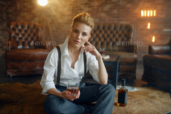 Woman sitting on the floor with whiskey and cigar - Stock Photo - Images