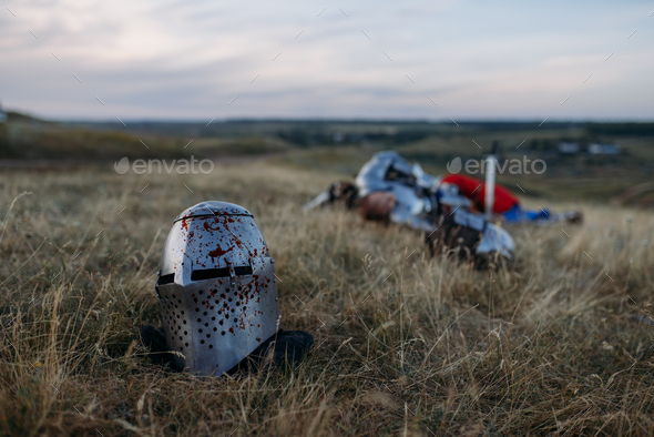Helmet in blood, dead knight on background - Stock Photo - Images