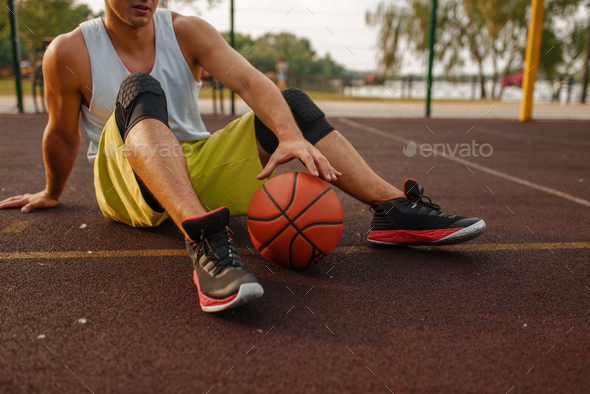 Basketball player with ball sitting on the ground - Stock Photo - Images