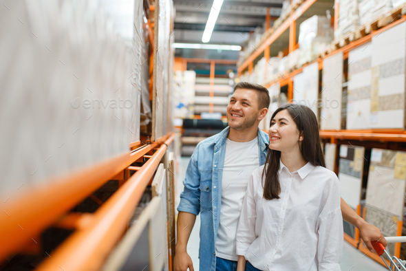 Young couple choosing ceramic tile, hardware store - Stock Photo - Images