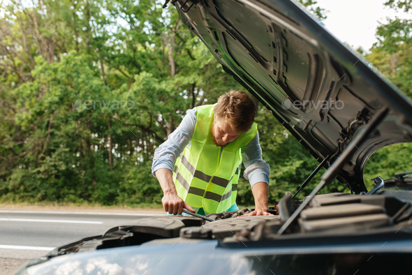 Man in reflective vest at opened hood, breakdown - Stock Photo - Images
