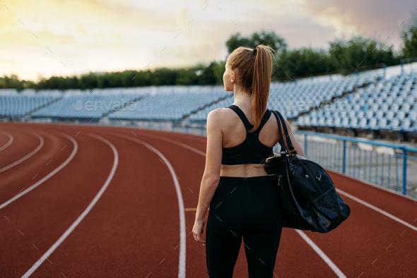 Female runner holds sport bag, training on stadium - Stock Photo - Images