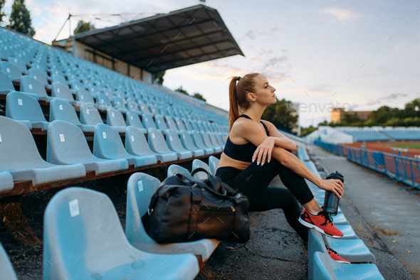 Female runner sitting on tribune and drinks water - Stock Photo - Images