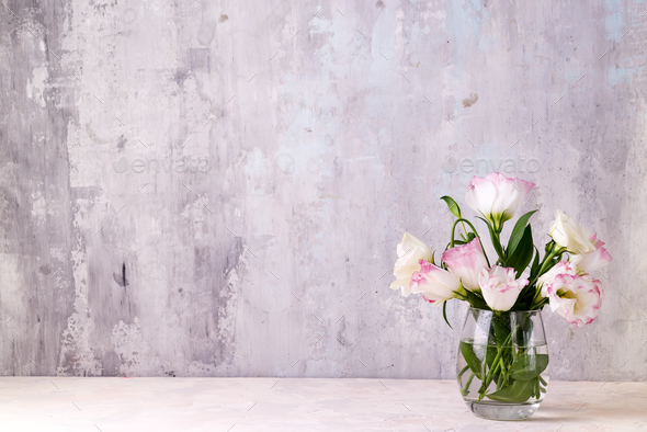 Eustoma flowers in vase on table near stone wall, space for text. Blank for postcards - Stock Photo - Images