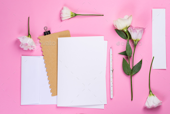 Flowers composition. Paper blank and notebook with eustoma pink flowers on pink background. Flat lay - Stock Photo - Images