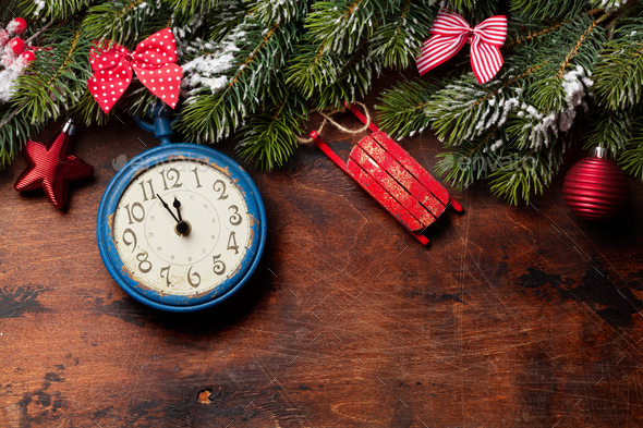 Christmas fir tree and alarm clock over old wood - Stock Photo - Images