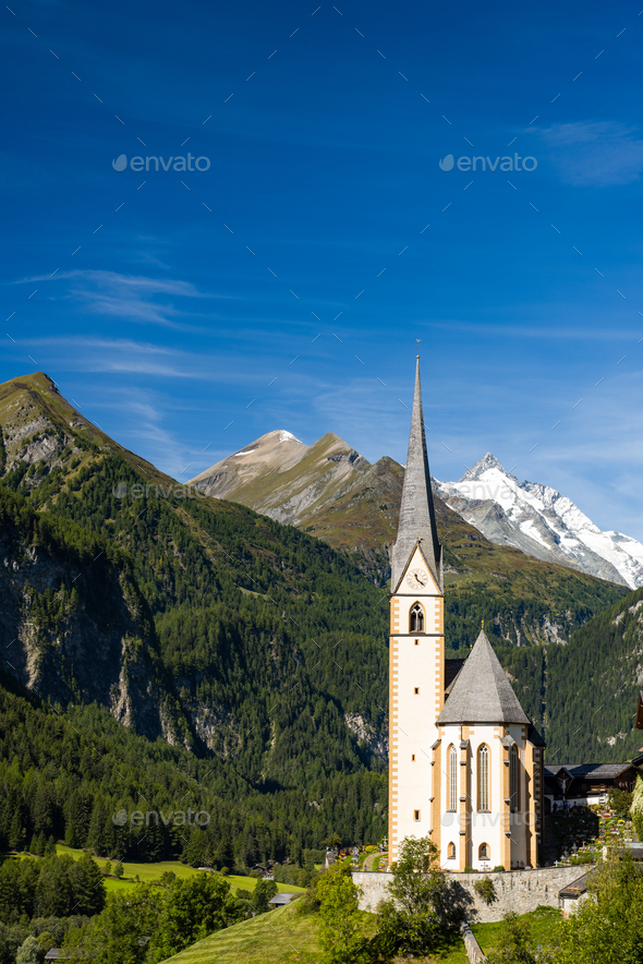 Pitcuresqe Church in Austria Village. High Alps Mountains in Bac - Stock Photo - Images