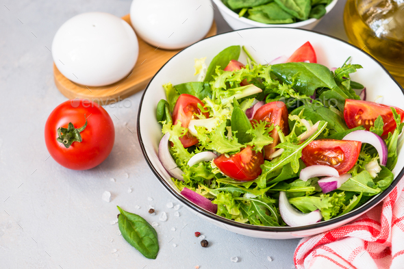Green salad from fresh leaves and tomatoes - Stock Photo - Images