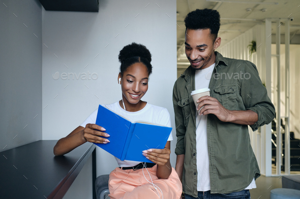 Young African American students happily reading book together in modern co working space - Stock Photo - Images