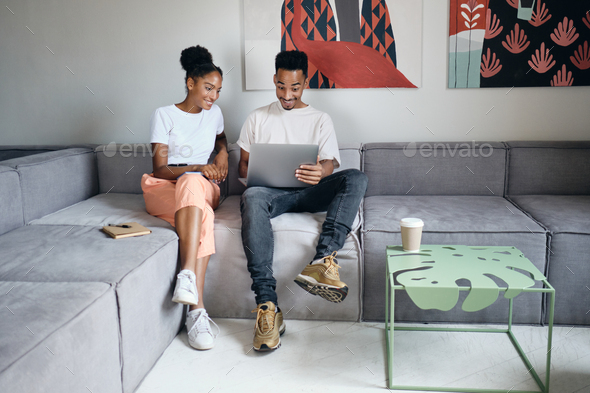 Attractive African American couple joyfully working on laptop together on sofa at office - Stock Photo - Images