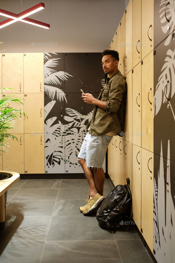 Young serious casual African American man with cellphone thoughtfully looking away in locker room - Stock Photo - Images
