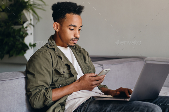 Serious African American guy with laptop thoughtfully using cellphone in modern co-working space - Stock Photo - Images