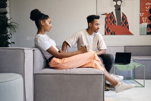 Young attractive casual African American couple thoughtfully talking during coffee break in office - Stock Photo - Images