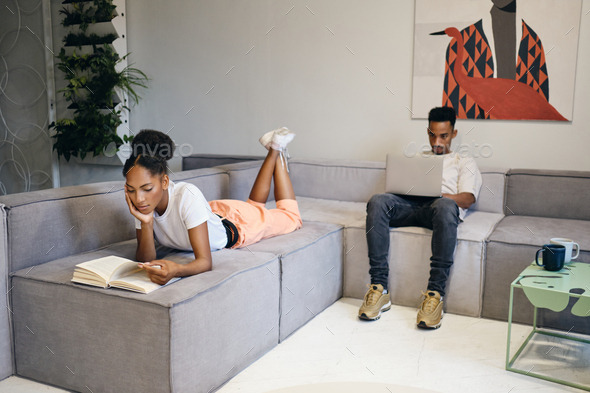 Young attractive African American couple thoughtfully working at modern home - Stock Photo - Images